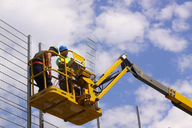 two construction workers in aerial lift